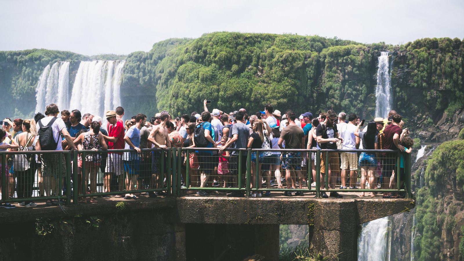 滝の上の遊歩道に群がるツアー客(南米大陸)のフリー素材