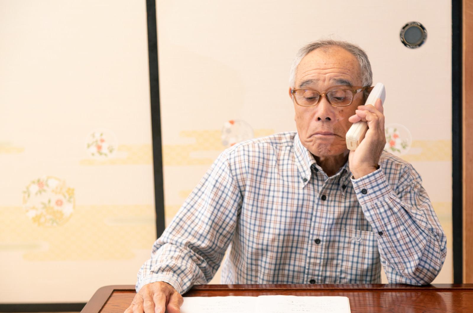 「老人会の名簿をチェックしながら電話をかける爺さん」の写真[モデル:まーちゃん]
