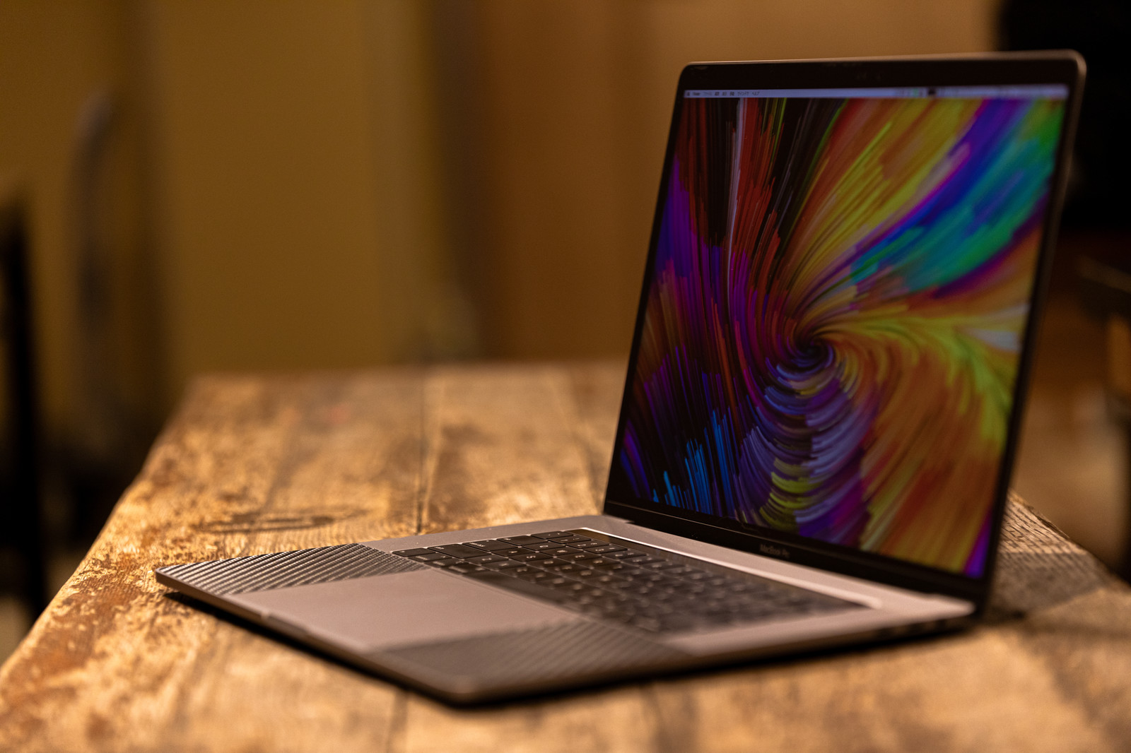 「作業台に無造作に置かれたMacBook Pro」の写真