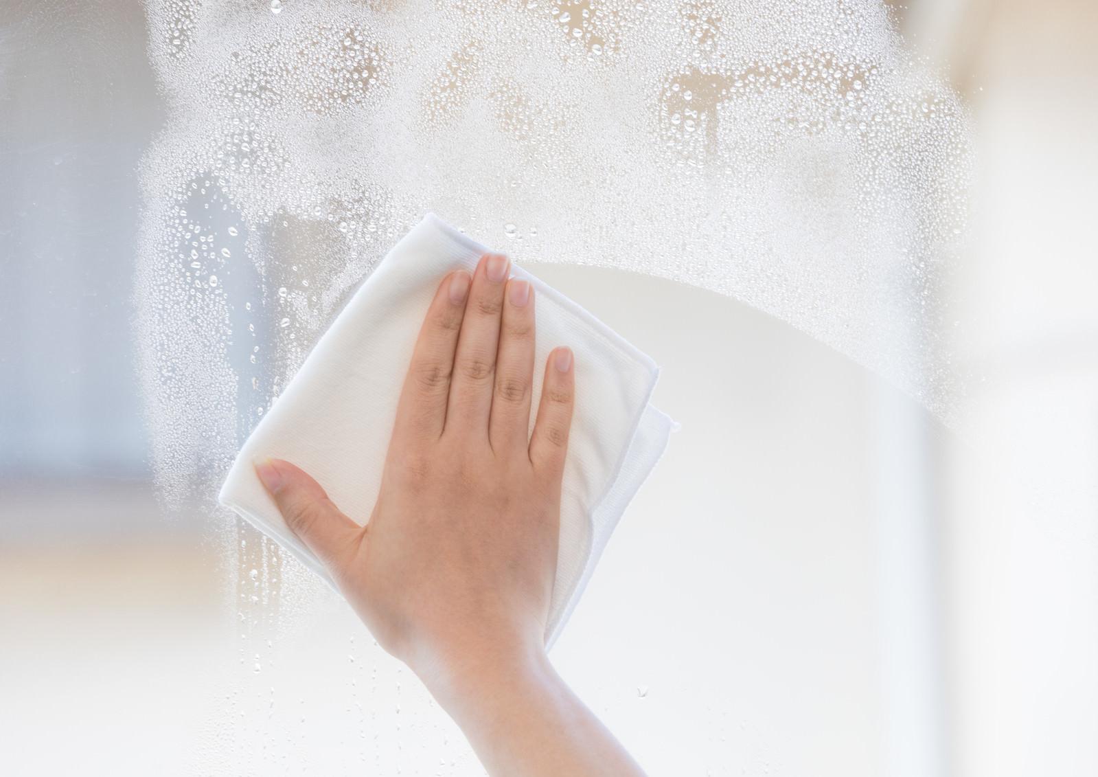 「ガラス窓を雑巾で拭く様子」の写真