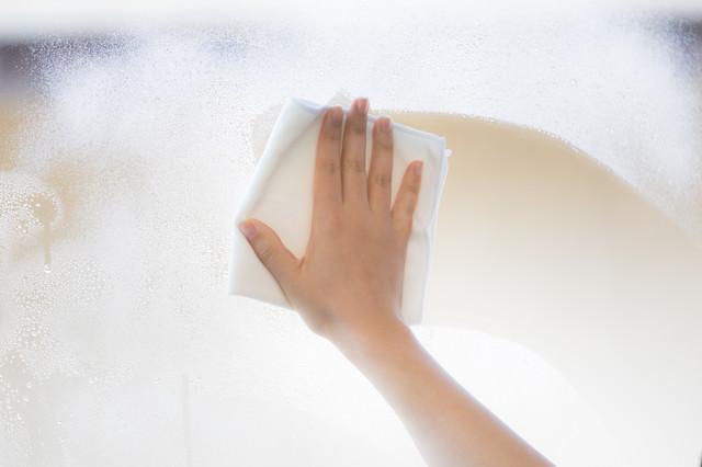 水洗いしたガラス窓を拭くの写真