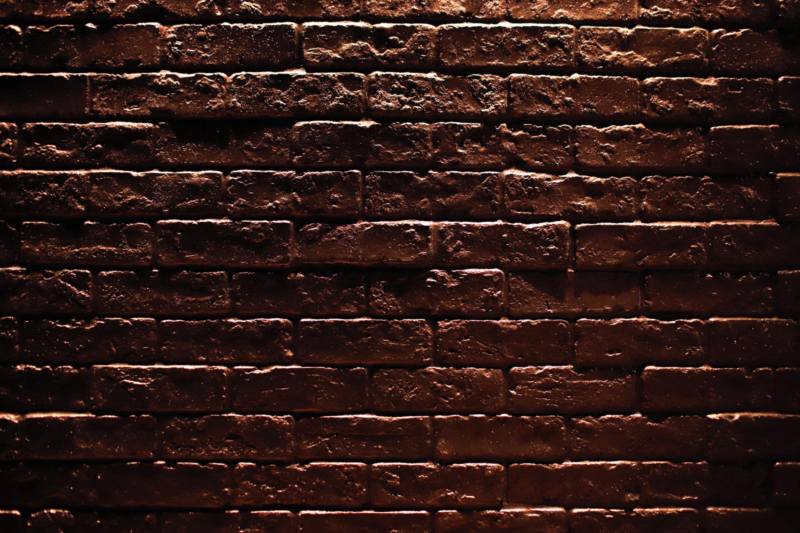 「暗闇に浮かび上がるレンガの壁(テクスチャ)」の写真