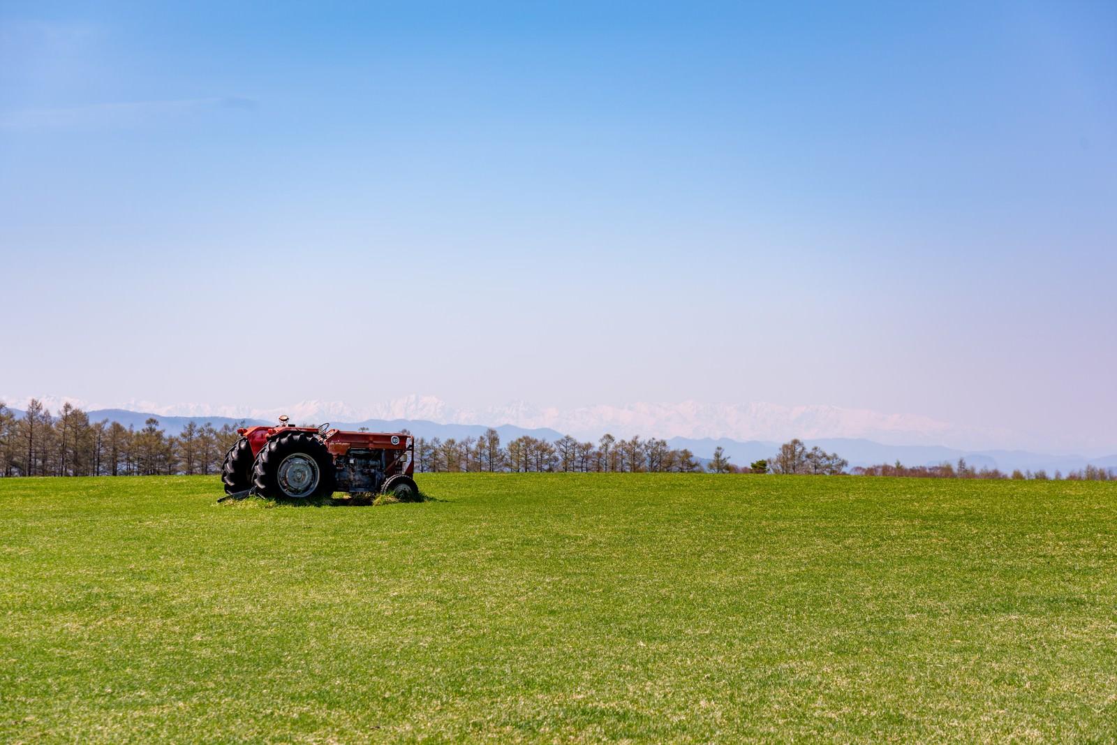 「広大な牧草地とトラクター」の写真