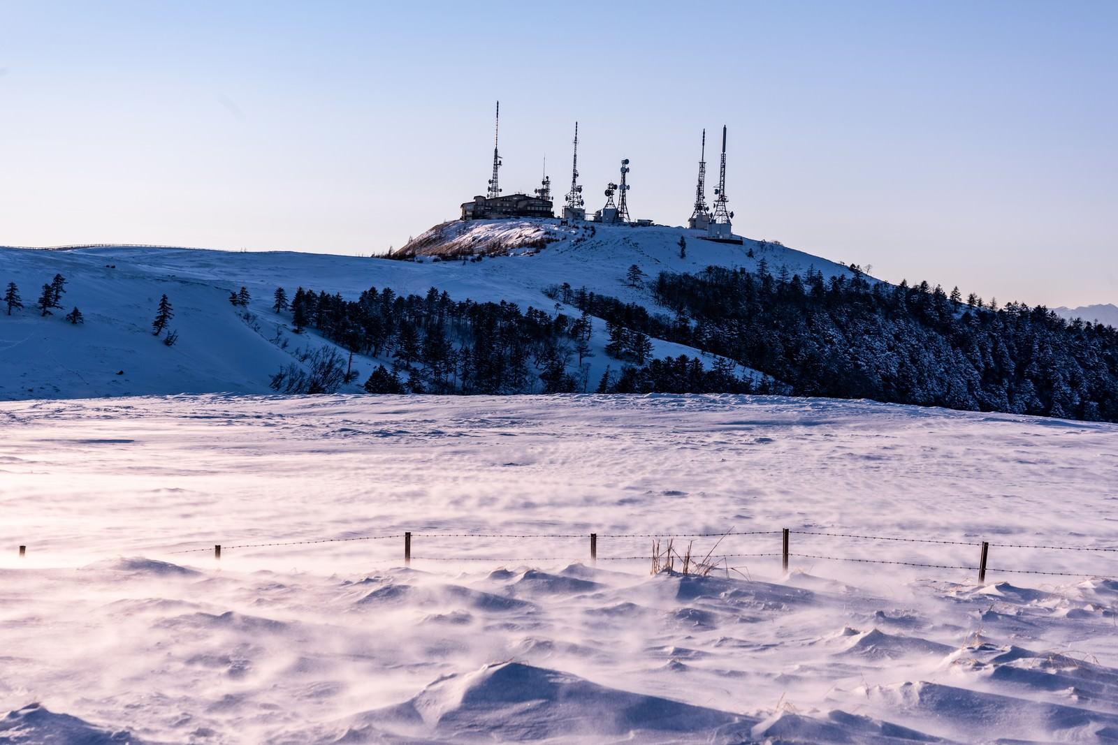 「積雪の高台にそびえる電波塔」の写真