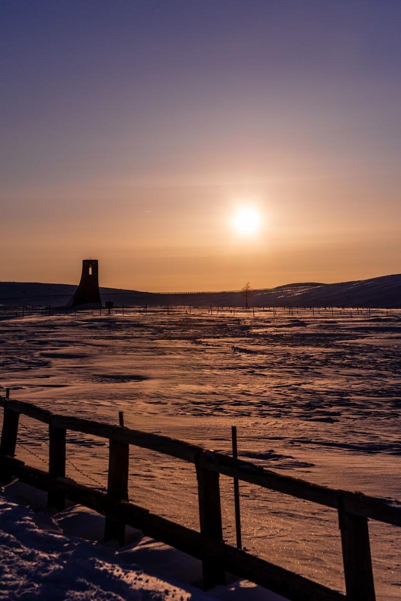 「夕刻の雪原に立つ避難塔」の写真