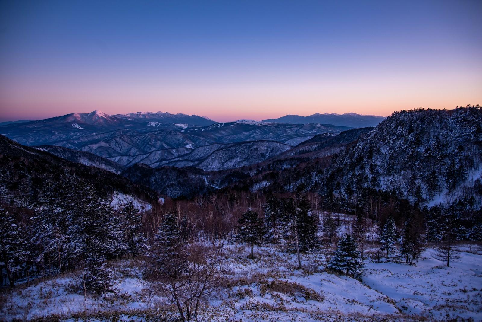 「焼けた空と雪化粧の山々」の写真