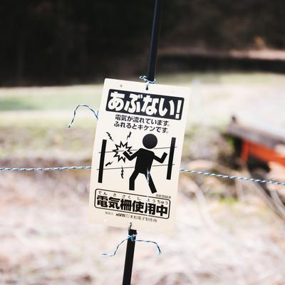 電気柵使用中の警告看板の写真