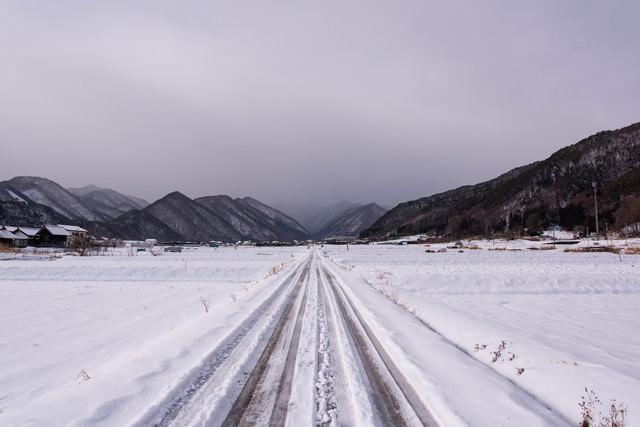 積雪した冬の田園を進む一本道の写真