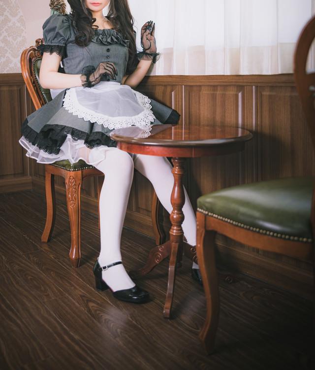 レトロな椅子に座るメイドさんの写真