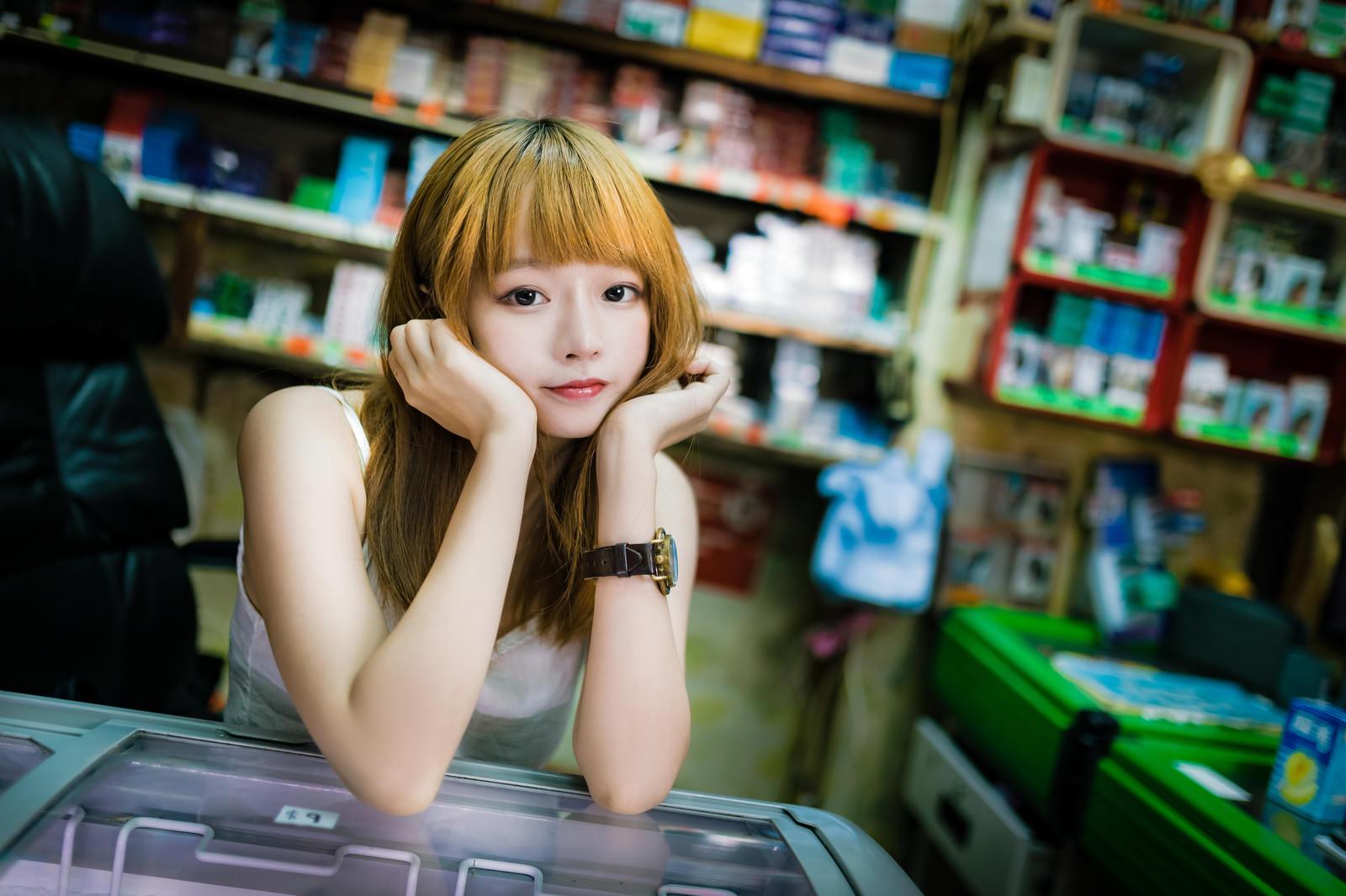 「香港の商店で店番をするプリン髪の美少女」の写真