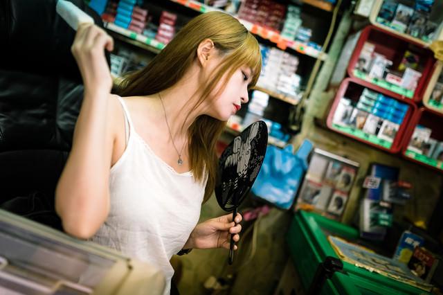 暑くてうちわで涼む店番女子の写真