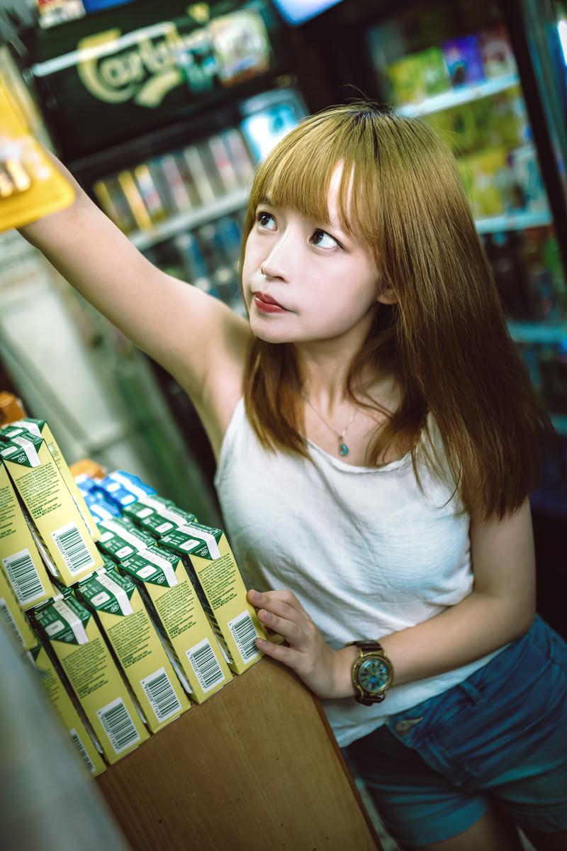 「手が届かない棚上の商品を取ろうとする女子」の写真[モデル:まみち]