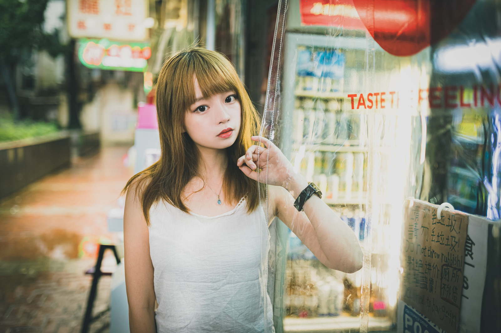 「外の様子を見る店番女子(香港の商店)」の写真[モデル:まめち]