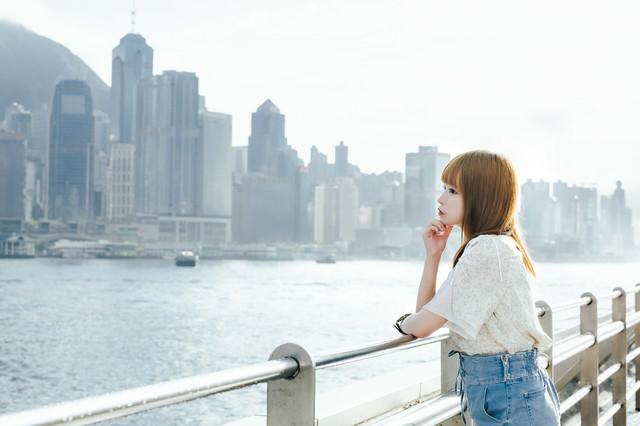 ビクトリアハーバー(香港)を見つめながら黄昏れる失恋美女の写真