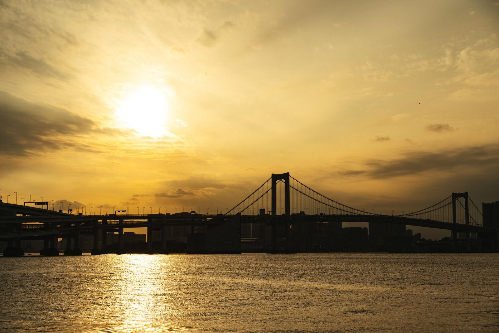 「夕日に照らされる海面と橋のシルエット | 写真の無料素材・フリー素材 - ぱくたそ」の写真