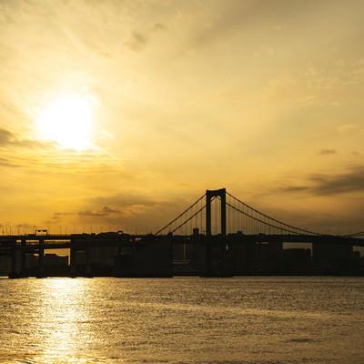 夕日に照らされる海面と橋のシルエットの写真