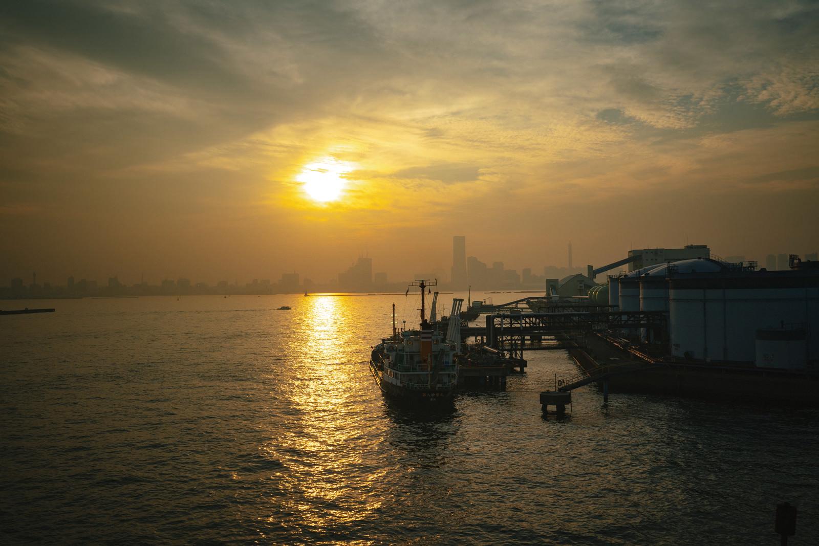「工業地帯から見る夕日と街並み」の写真