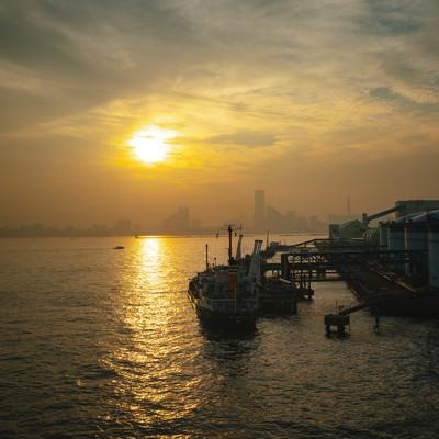 工業地帯から見る夕日と街並みの写真