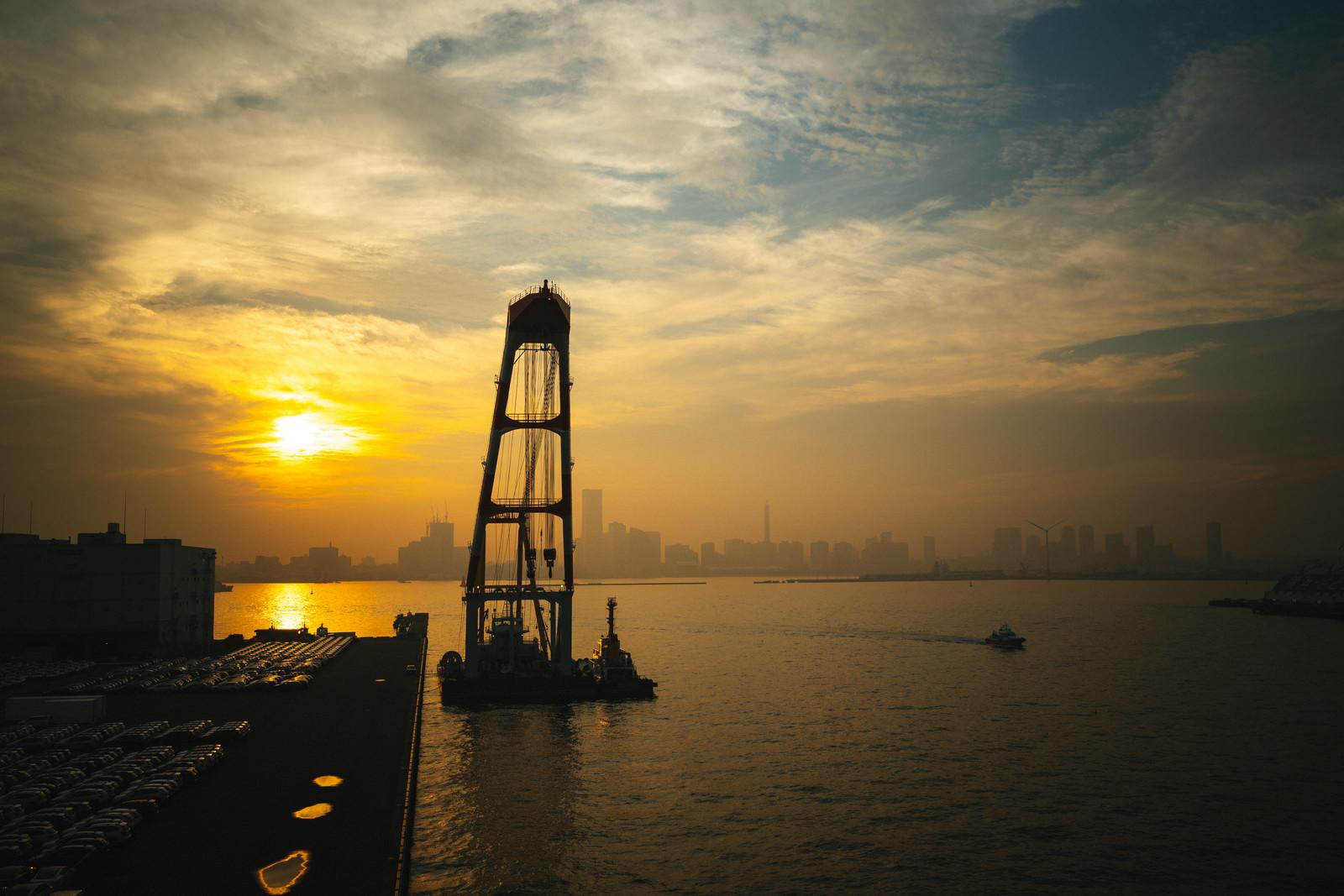 「港から見る夕日と街並み」の写真