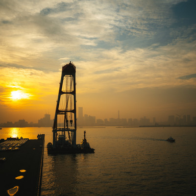 港から見る夕日と街並みの写真