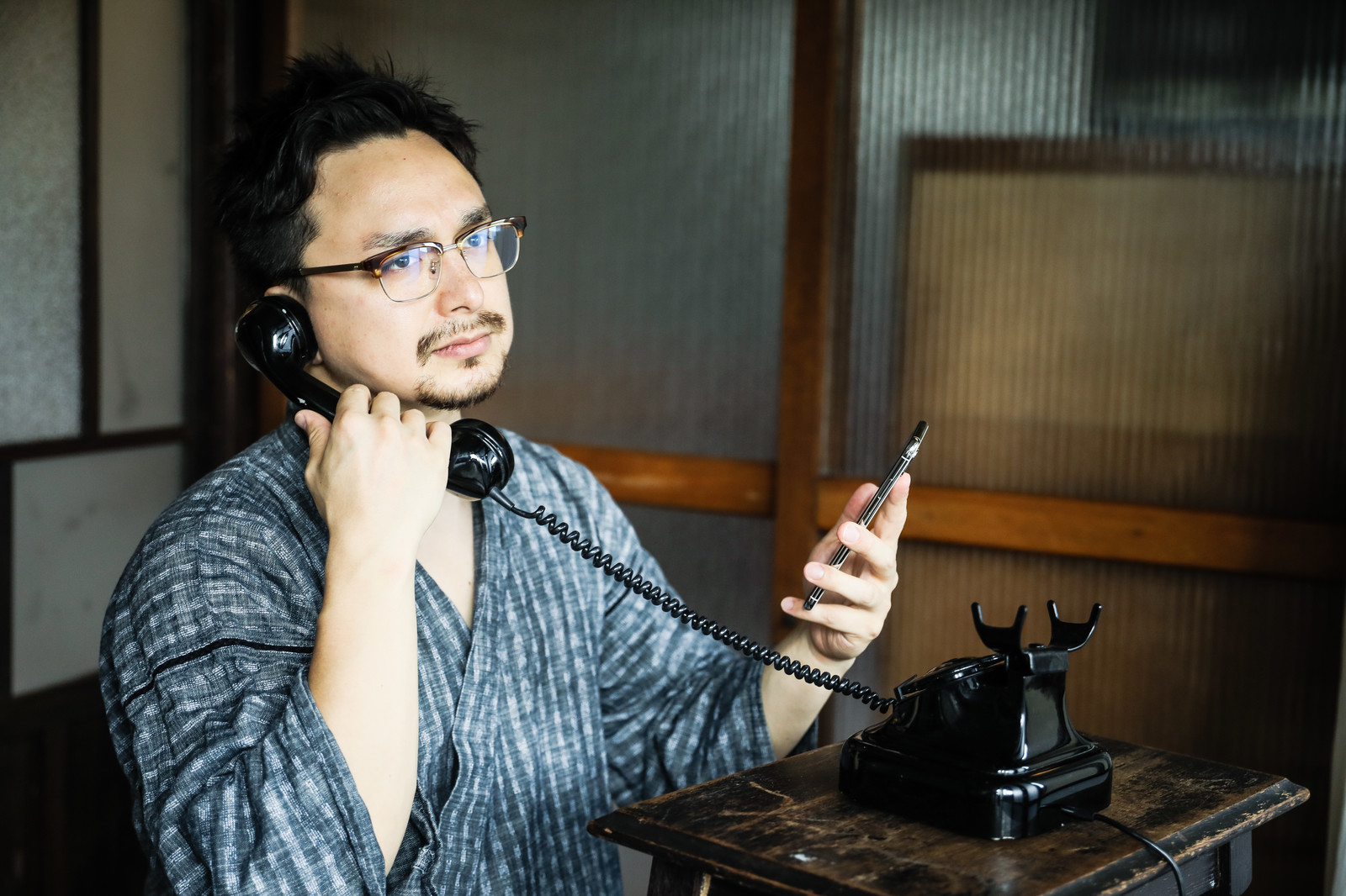 「スマホで連絡先を確認しながら黒電話を使う外国人観光客」の写真[モデル:Max_Ezaki]