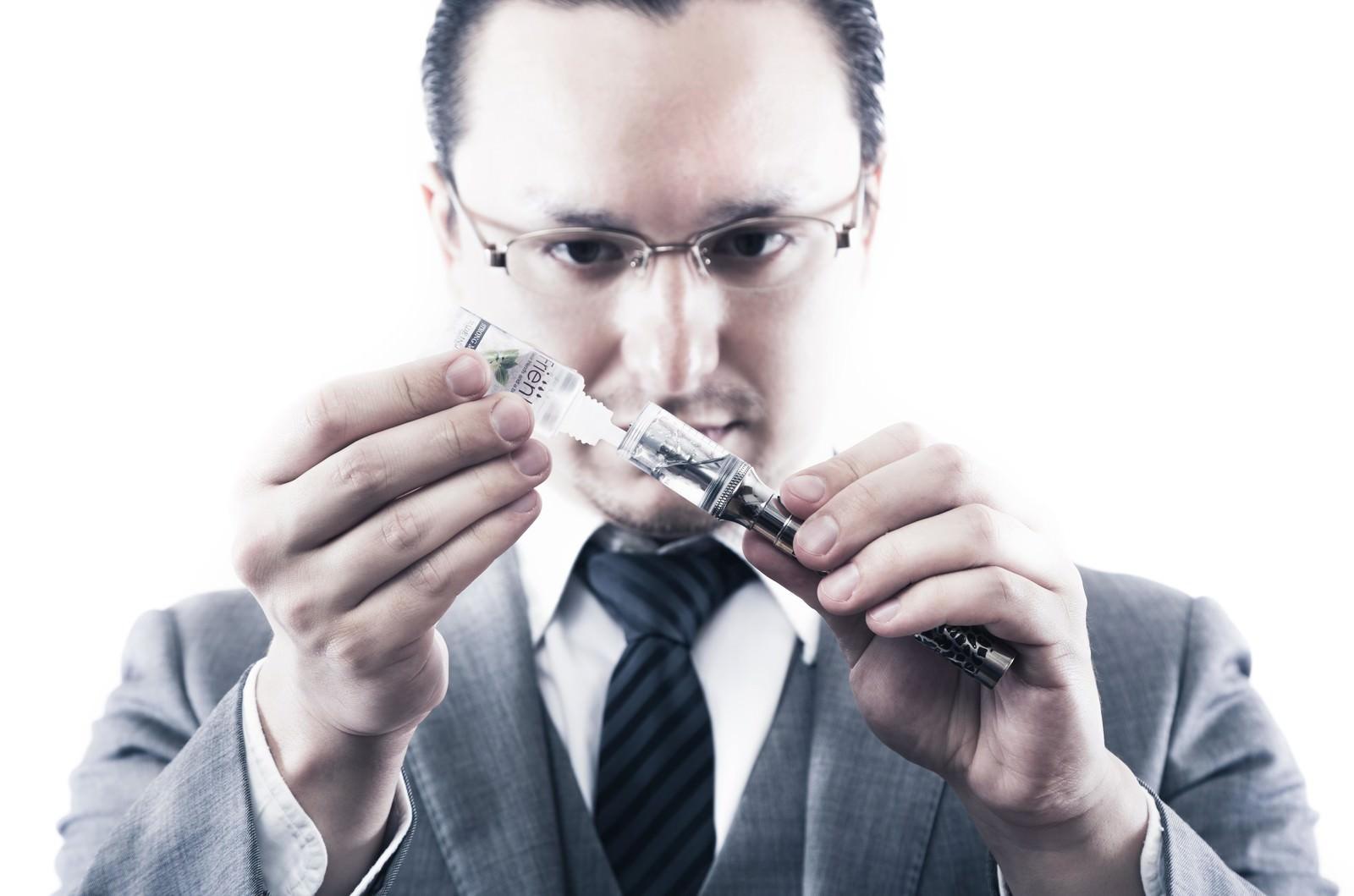 「電子タバコにリキッドを補充するビジネスマン」の写真[モデル:Max_Ezaki]