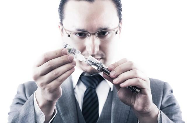 電子タバコにリキッドを補充するビジネスマンの写真