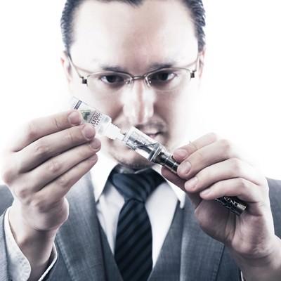「電子タバコにリキッドを補充するビジネスマン」の写真素材
