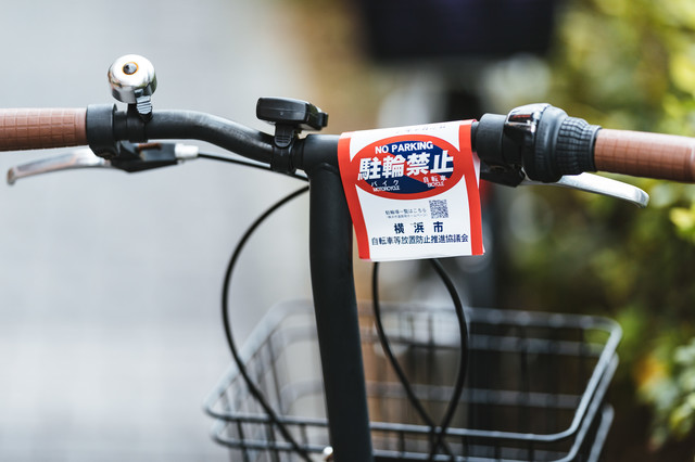 自転車のハンドルに付けられた駐輪禁止の警告書の写真