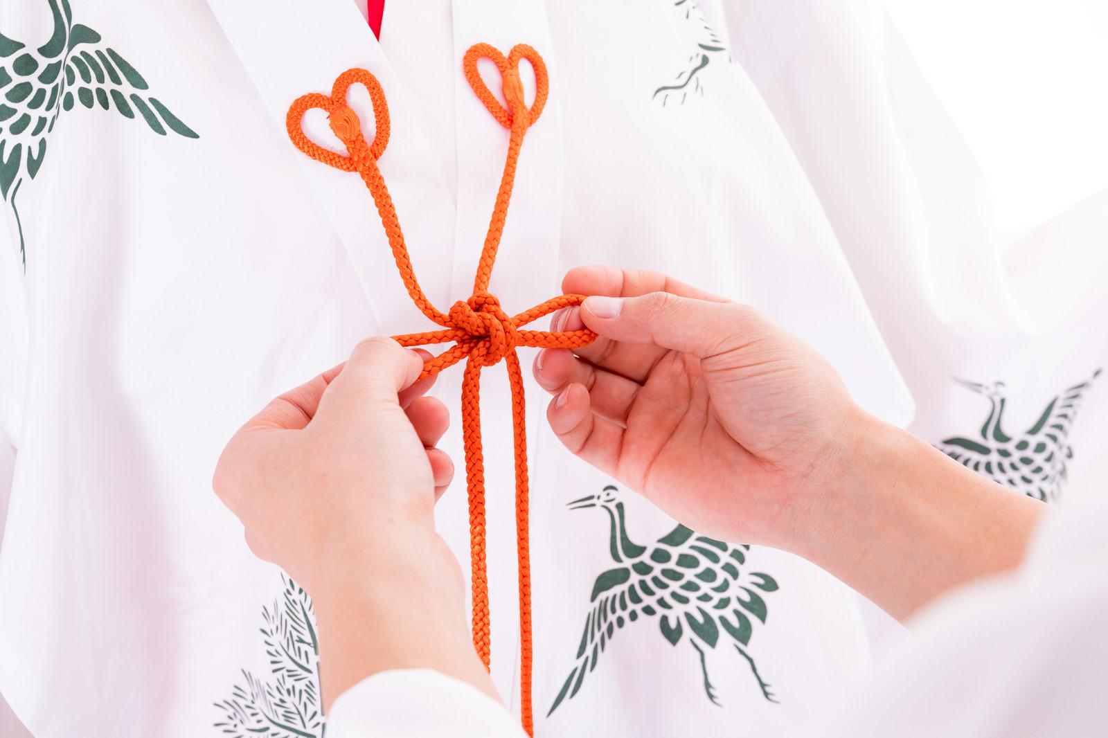 「巫女装束「千早」を結ぶ手元」の写真