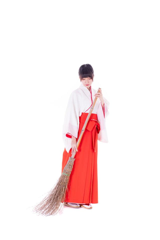 竹箒(たけぼうき)で掃除中の巫女さんの写真