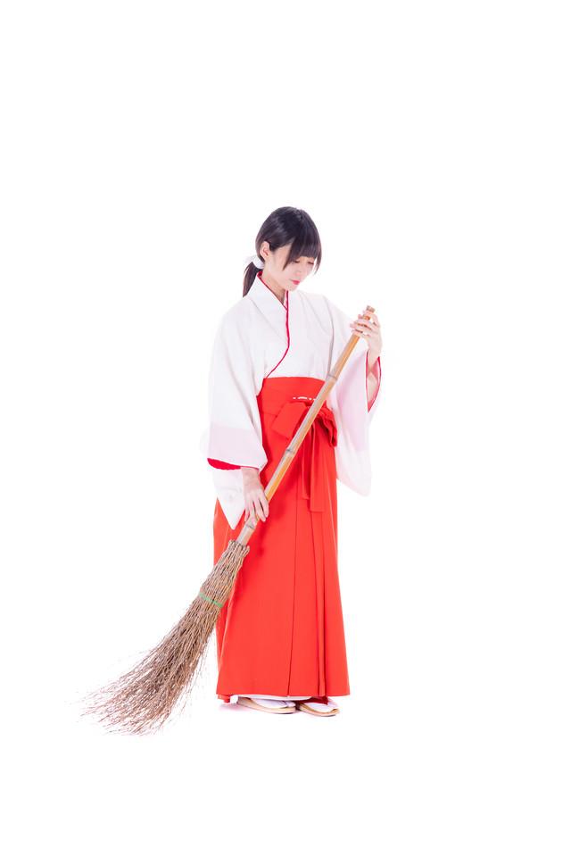 竹ほうきを持ち掃除をはじめる巫女さんの写真