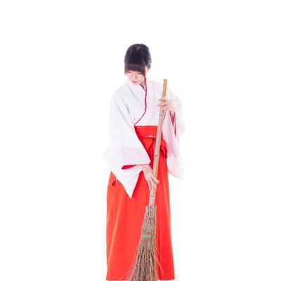 巫女さんが竹ほうきで掃除する様子の写真