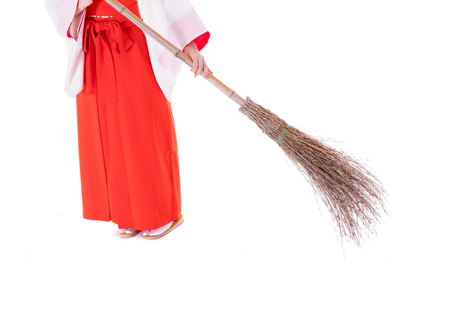 「竹ほうきで掃き掃除をする巫女の足元」の写真[モデル:緋真煉]