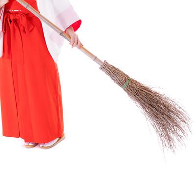 竹ほうきで掃き掃除をする巫女の足元の写真