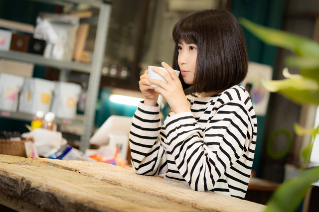 挽きたてのコーヒーを飲む女性の写真