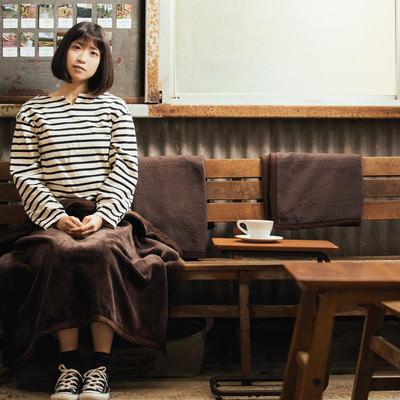 レトロな雰囲気のカリオモンズコーヒーの店内で一息つく女性の写真