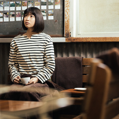 レトロな雰囲気のカフェでコーヒーで一息つく女性の写真