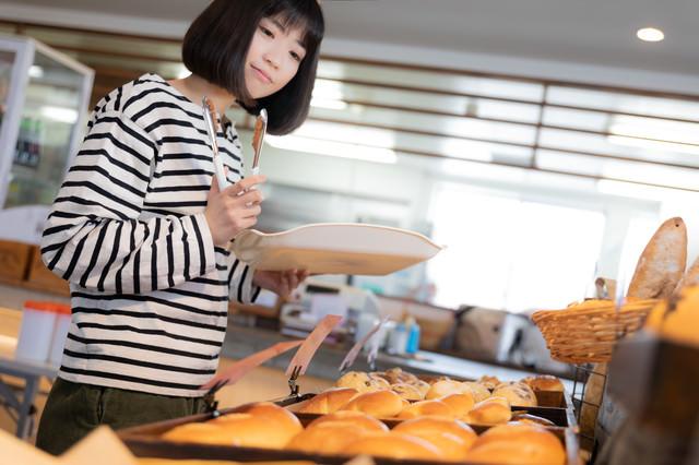 焼きたてのパンを選ぶ女性の写真