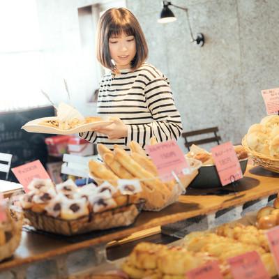手作りパンのお店でトレイを手に取り店内を歩く女性の写真