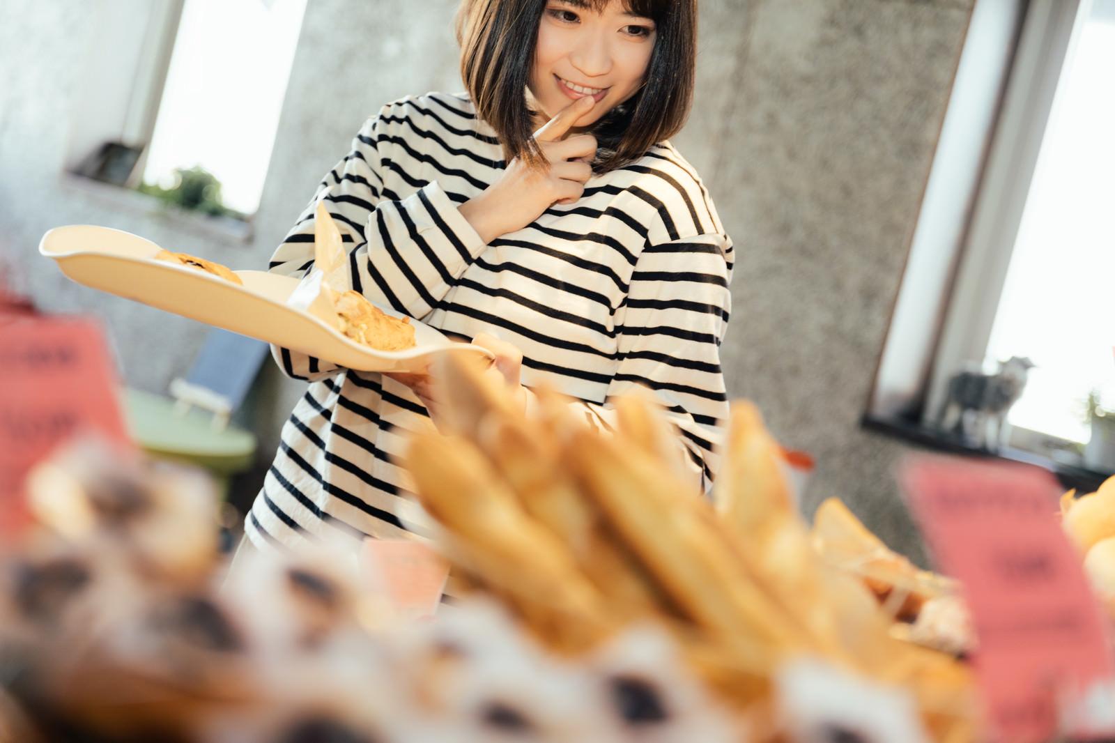 「お腹が空いたからもうひとつ食べちゃおう」の写真[モデル:塩田みう]