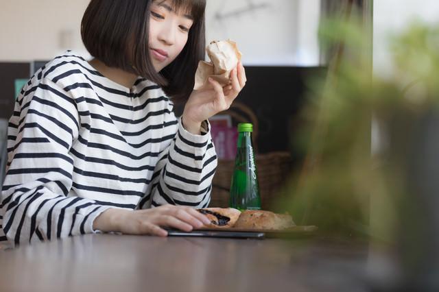 フードコートでパンを食べながらスマホを見る女性の写真