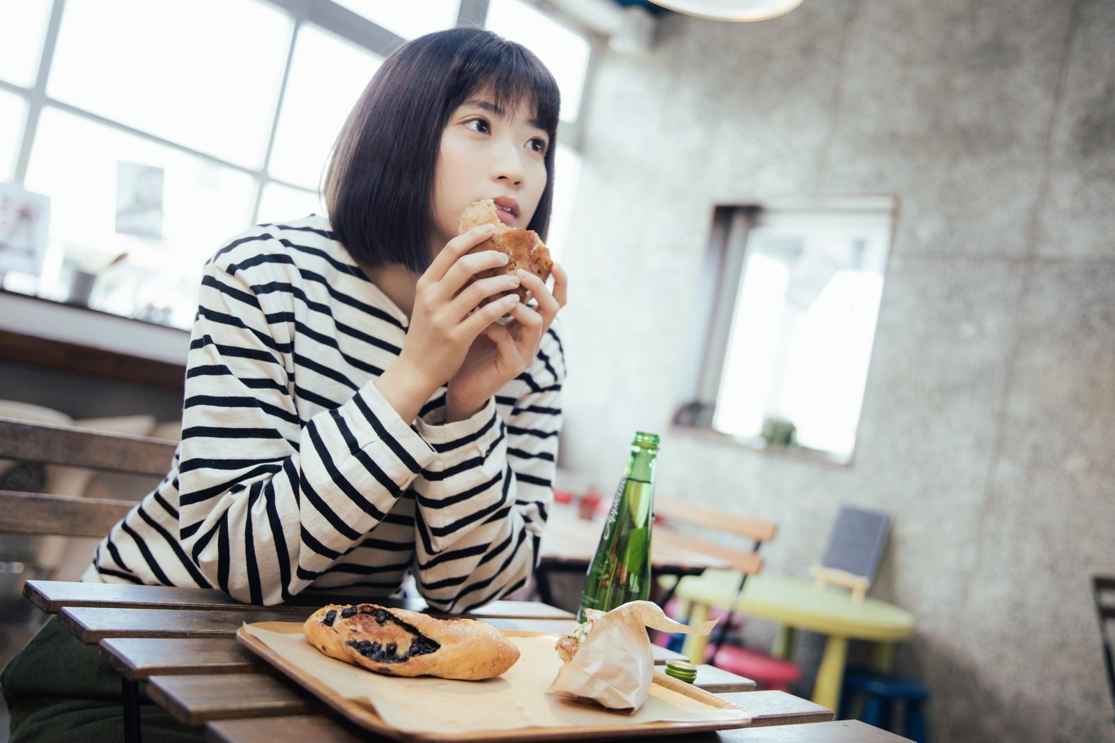 「フードコートでおやつに菓子パンを食べる女性」の写真[モデル:塩田みう]