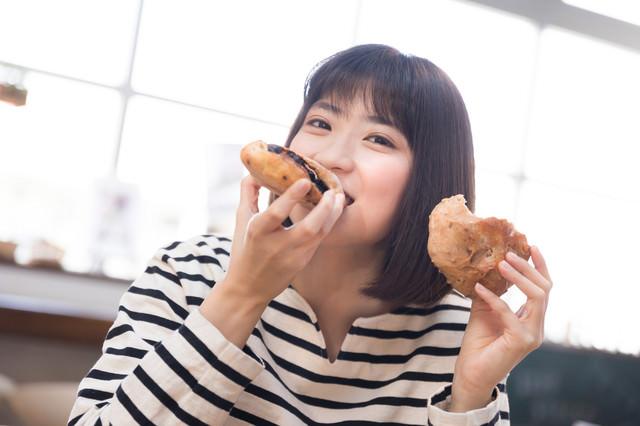 手作りパンを頬張る女性の写真
