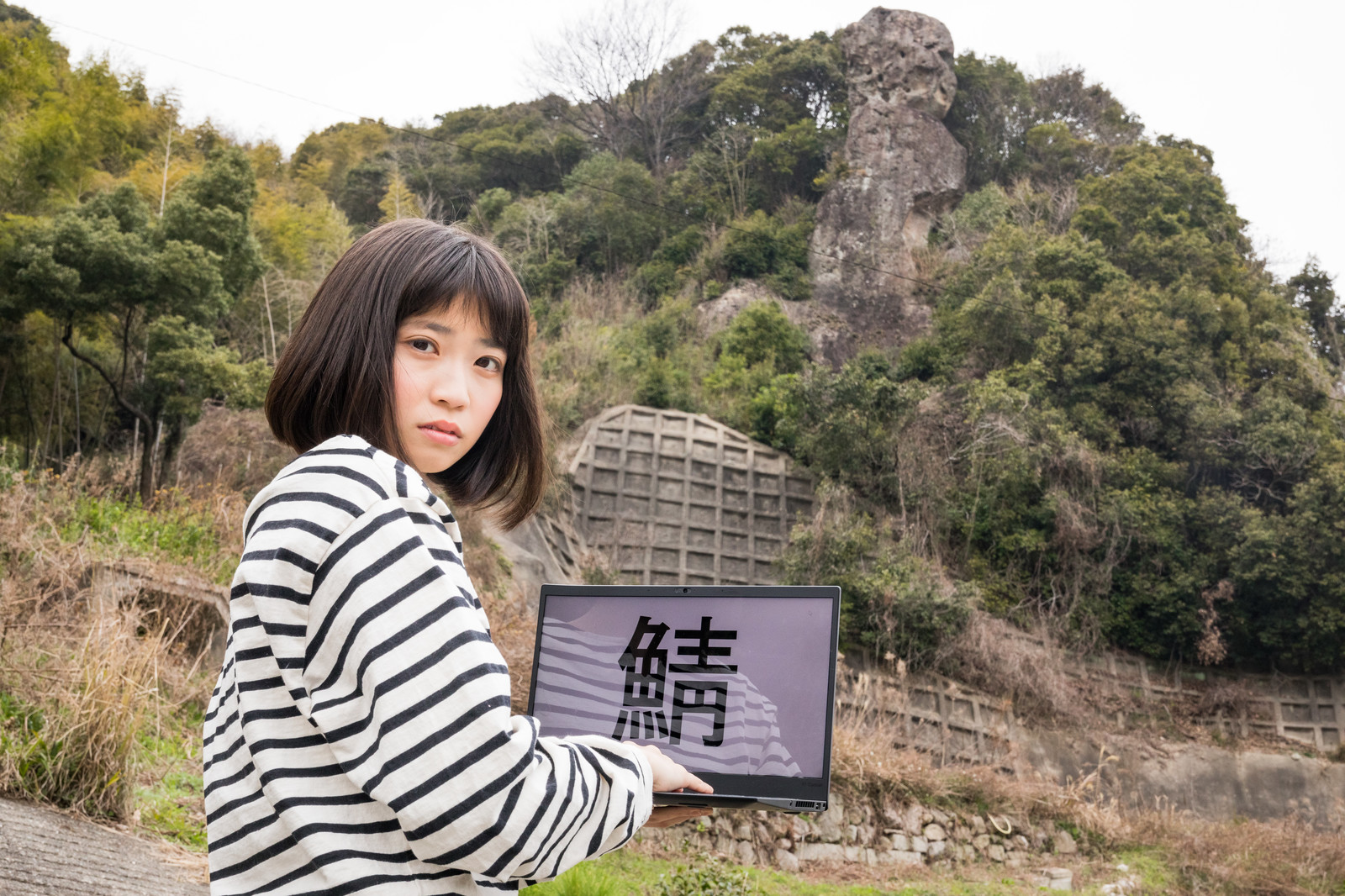 「鯖くさらかし岩の近くでサーバーにアクセスする女性」の写真[モデル:塩田みう]