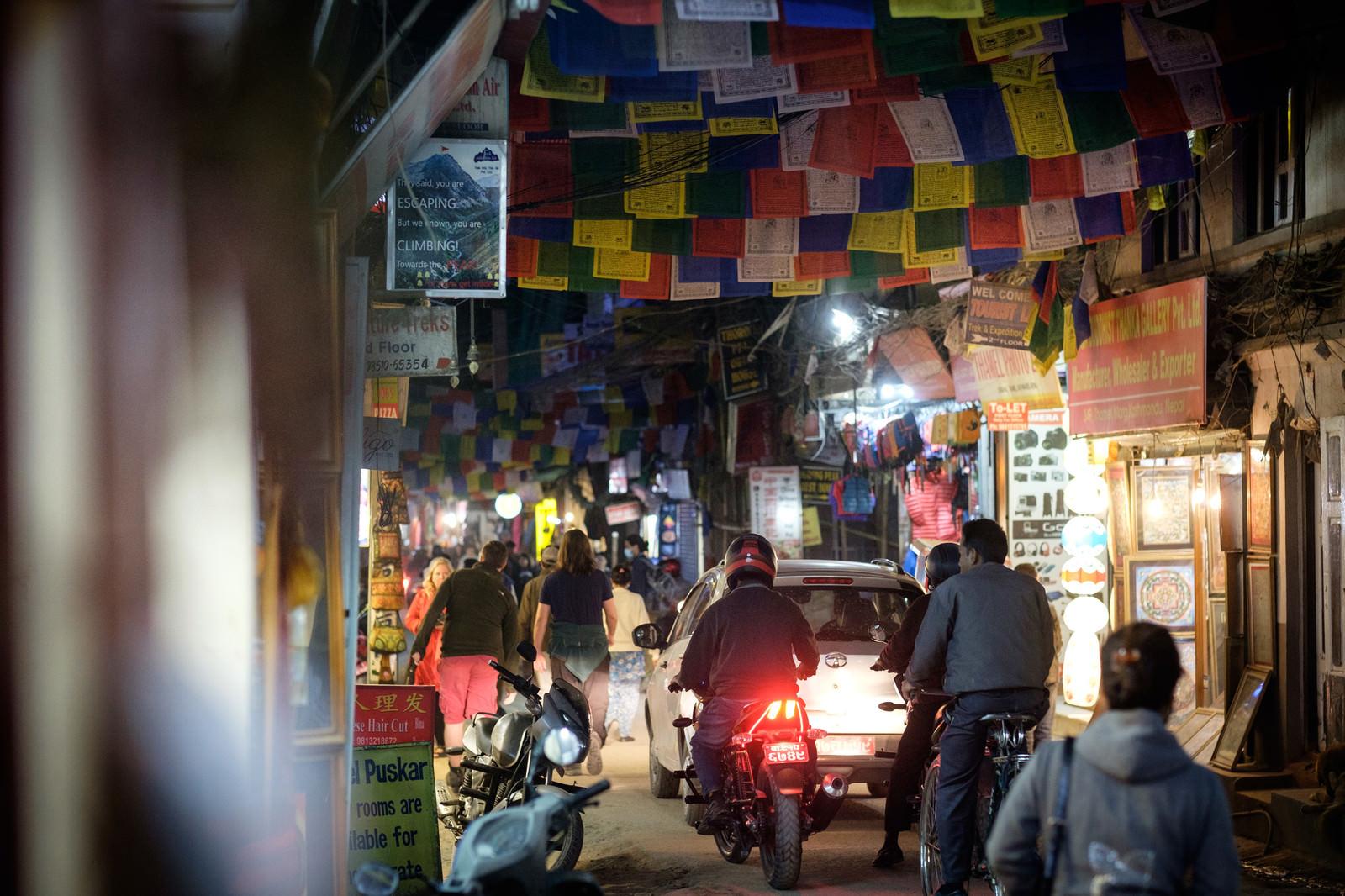 「人でごった返す細い商店街に車とバイクが侵入する(ネパール)」の写真
