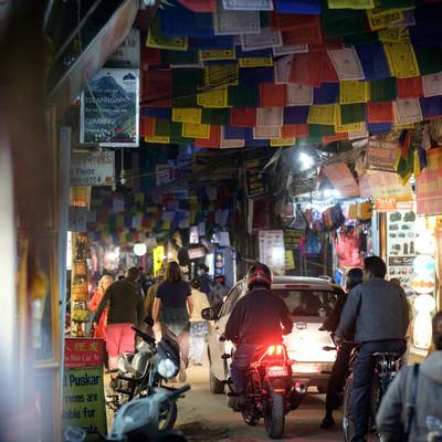 「人でごった返す細い商店街に車とバイクが侵入する(ネパール)」の写真素材