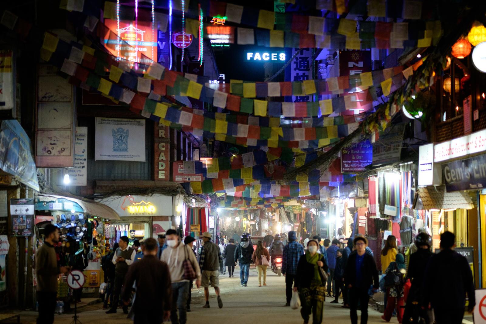 「カラフルな紙が吊るされたカトマンズの繁華街」の写真