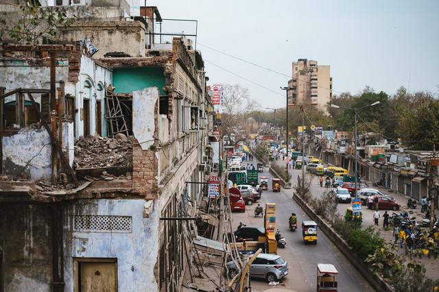 倒壊しそうな建物と交通量の多い大通りの写真
