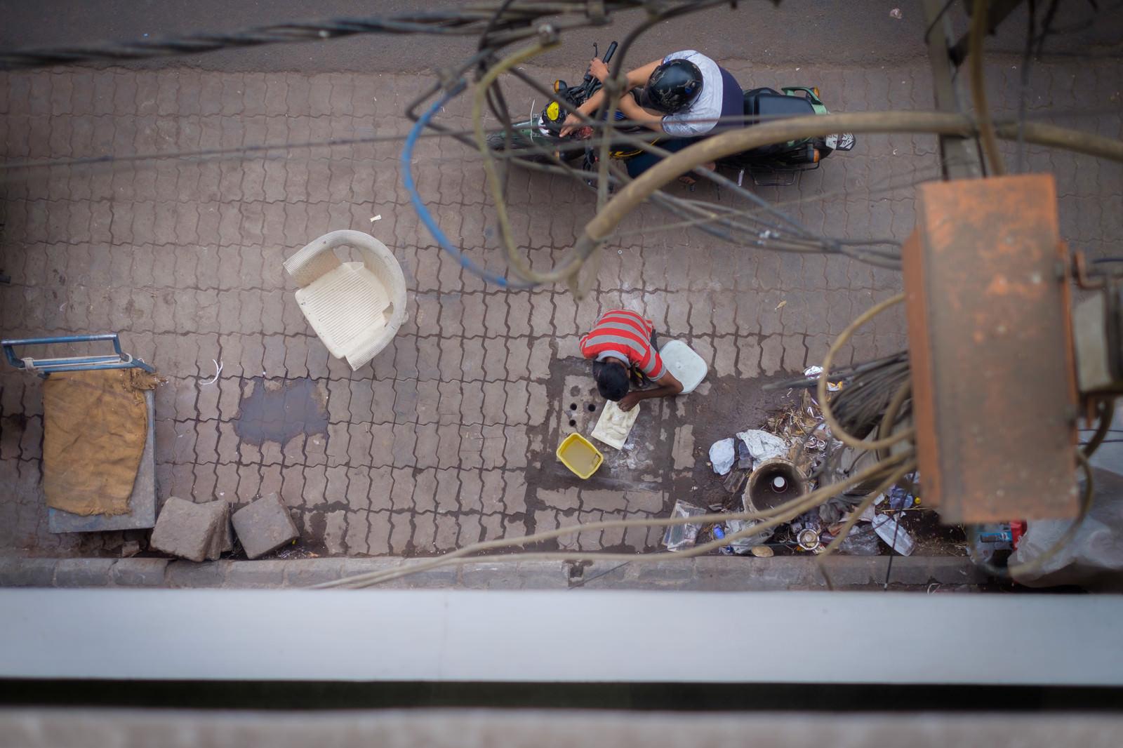 「路肩で洗い物をする少年(インド)」の写真